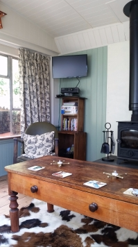 Looking into the corner of the lounge. There is a wall mounted smart TV along with a BluRay player and docking station.